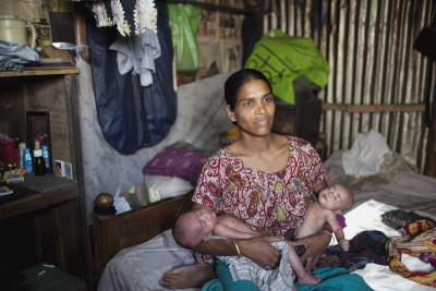 A Bangladeshi woman holds her twins at her home in Korail slum. Photo: Chantal Anderson