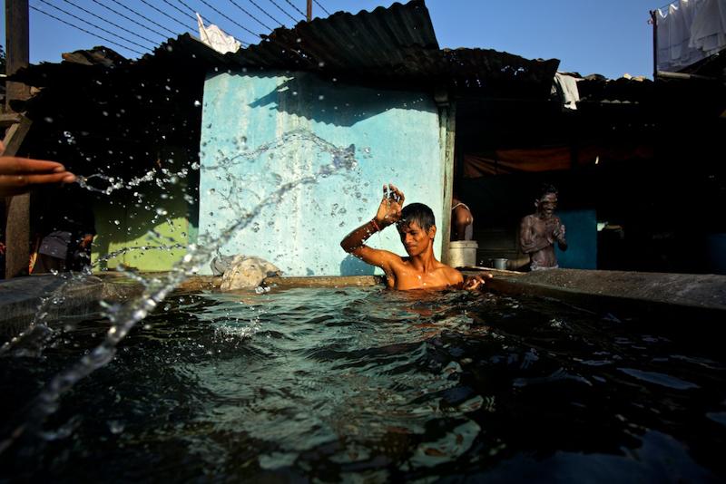 A boy splashes water on a boy having bath. A boy splashes water on another boy bathing in a wash pen.