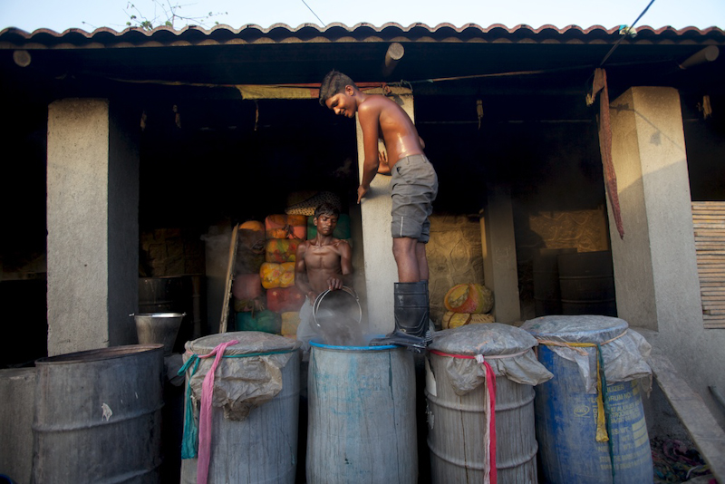 A man stands on a tumbler filled with clothes for washing. A dhobi immerses clothes in a vat filled with boiling caustic soda.