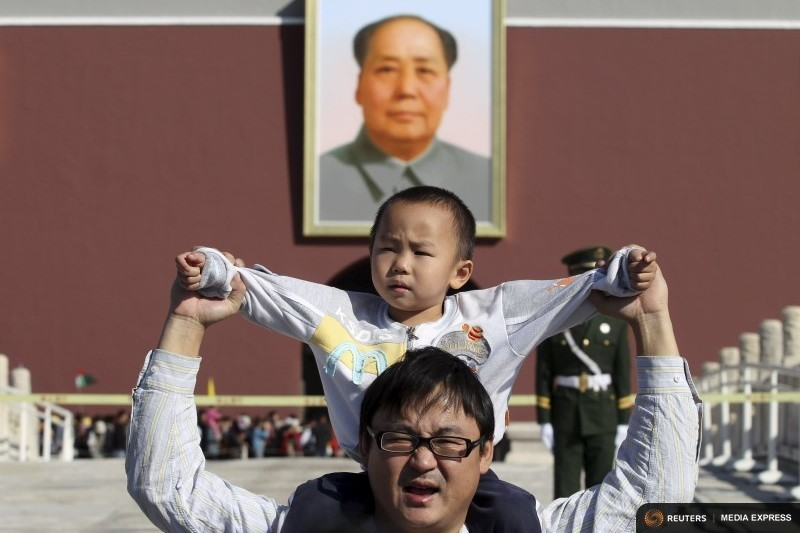 A boy sits on his father's shoulders as they pose for a photograph in front of the giant portrait of late Chinese chairman Mao Zedong on the Tiananmen Gate, in Beijing, China, October 2, 2011.  (Photo by Reuters.)