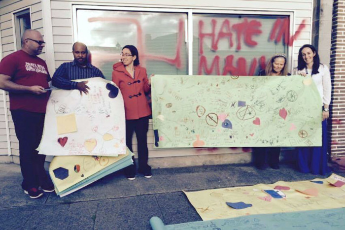Amor Spiritual Center's Rev. Allen Mosely (left) stands next to his husband Tony Winsely, who is also the choir director, as teachers offer posters with messages of love made by students at Beacon Hill International School. (Photo by Emma Moreno.)