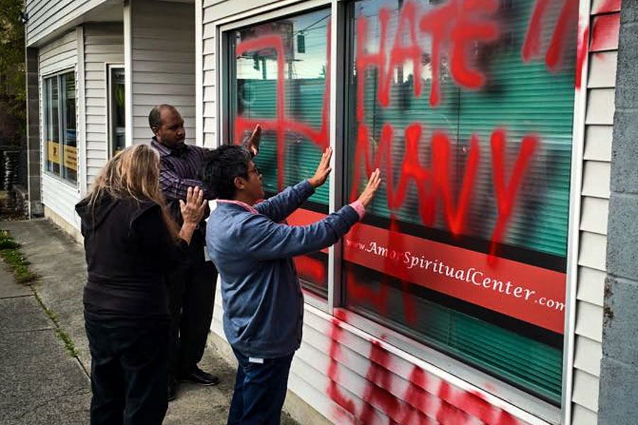 People pray before cleaning up graffiti that defaced the Amor Spiritual Center. (Photo via Facebook.)
