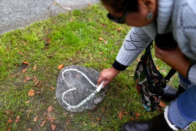 Xochitl Garcia draws a heart with chalk in front of the Amor Spiritual Center on Sunday. (John Lok/The Seattle Times)