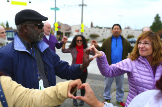 Frank Jones and Eileen Hershberg form a shape of a heart with their hands Sunday near the Amor Spiritual Center on Beacon Hill. They joined city council candidates and others in a love circle in response to hateful graffiti sprayed on the building's front window area. (Photo by John Lok / The Seattle Times)