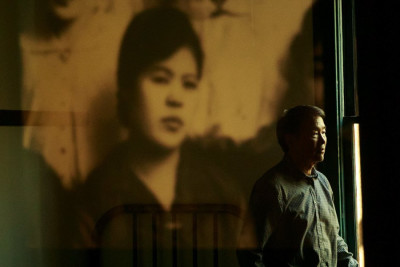 At the Wing Luke Museum last month, Densho Executive Director Tom Ikeda's reflection is seen in a display of historical images from the region. Ikeda talked about the Japanese American legacy project. (Erika Schultz / The Seattle Times)