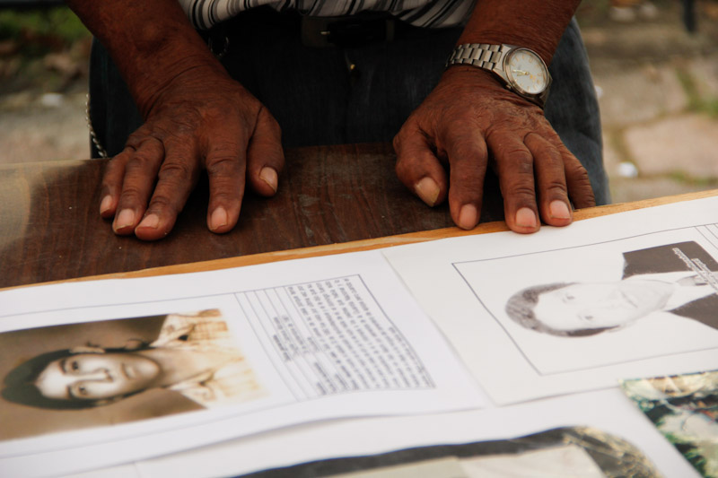 """An elder Salvadoran man who survived the armed conflict is preparing a poster memorializing slain family members for the annual """"Encuentro de Victimas"""" (Meeting of Victims) in San Salvador, El Salvador. (Photo by Alex Montalvo)"""