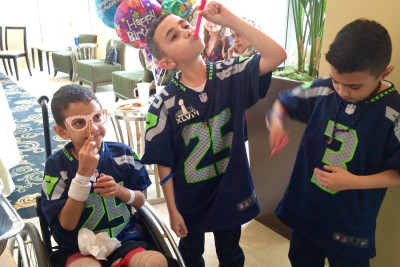 Shoulub (left) jokes around with new friends wearing matching Seahawks jerseys at the birthday party in Bellevue. Despite having the amputations just ten days prior, he was all smiles on Saturday. (Photo by Varisha Khan)