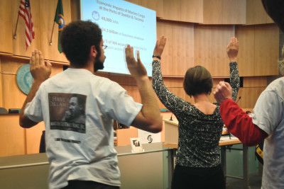 Demonstrators raise their arms in protest during a January meeting of the Seattle City Council to discuss police activity in response to Black Lives Matter. (Photo by Theo Nestor)