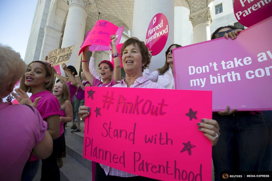 "Activists hold signs as they rally in support of Planned Parenthood on ""National Pink Out Day"" on the steps of City Hall in Los Angeles this week, in the face of conservative calls to pull federal funding for the controversial women's health organization. (Photo from REUTERS / Mario Anzuoni)"