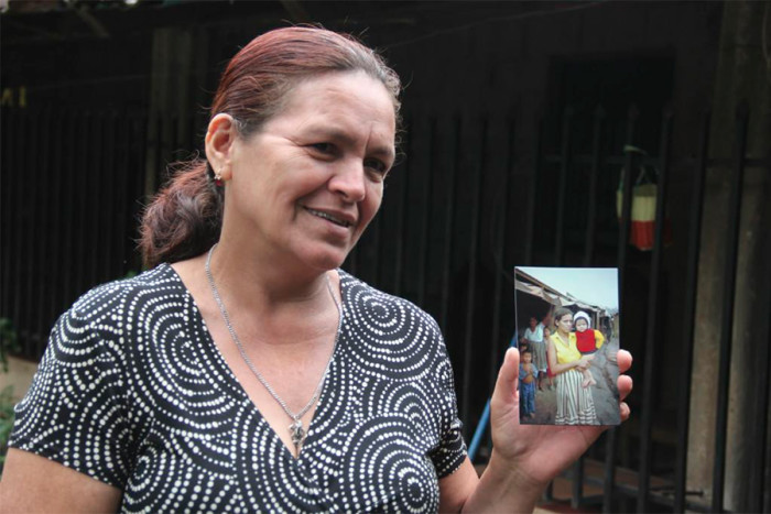 Dina Cabrera holds a photo of herself with her son taken in 1982 in the Mesa Grande refugee camp by Philippe Bourgois. Dina was five months pregnant during the November 1981 invasion. (Photo by Keny Sibrian via UW Center for Human Rights Twitter.)
