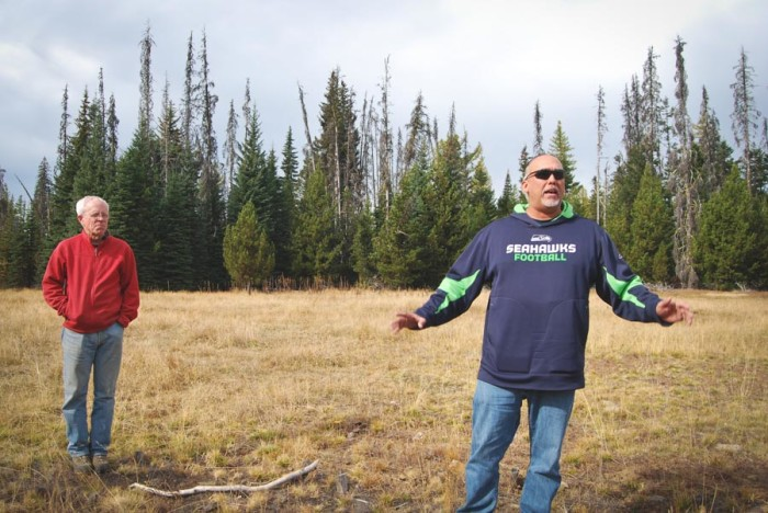 Steve Rigdon of Yakama Forest Products, right, and UW professor emeritus Tom Hinckley discuss the impacts of climate change and forest health while standing in a meadow on the Yakama reservation that was traditionally managed using fire. (Photo by Ana Sofia Knauf)