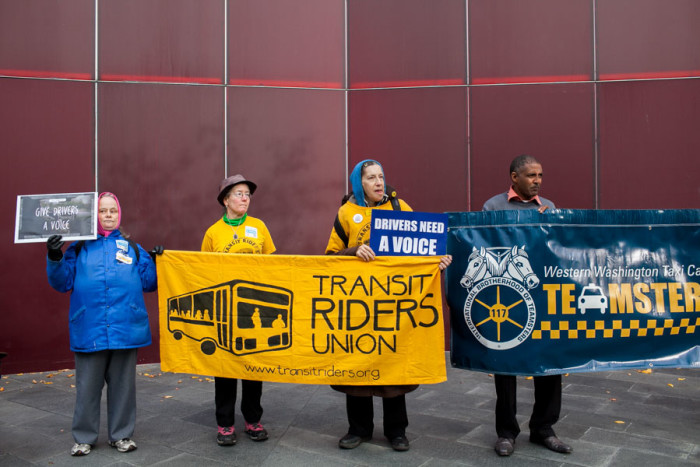 Members of the Transit Riders Union and Teamsters Local 117 stand in support during the Voice for Drivers rally today at Seattle City Hall. (Photo by Jovelle Tamayo)