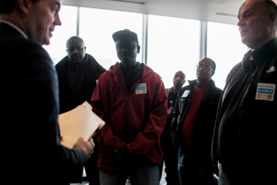 A representative from the Mayor's office accepts the Voice for Drivers petition from Uber, Lyft and other for-hire drivers. (Photo by Jovelle Tamayo)