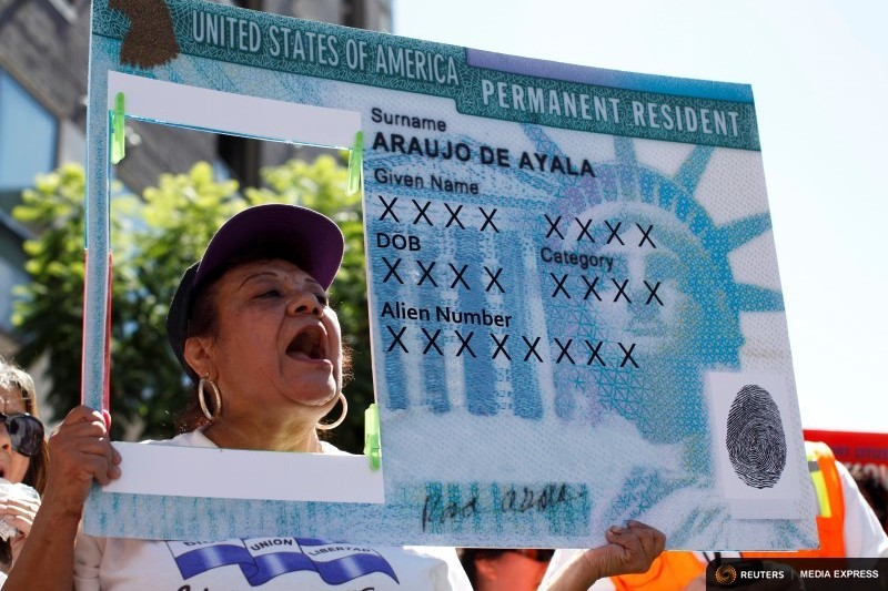 A woman holds a replica green card sign during a protest march to demand immigration reform in Hollywood. (Photo by Lucy Nicholson for Reuters/file.)