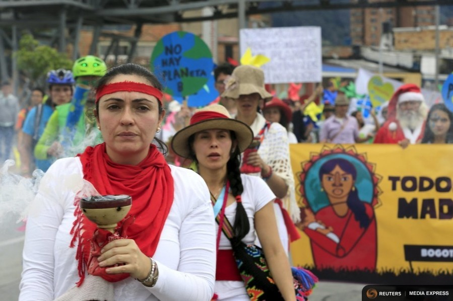Women activists take part in a march ahead of the 2015 Paris Climate Change Conference, known as the COP21 summit, in Bogota, Colombia November 29, 2015.  (Photo by Jose Miguel Gomeza for Reuters.)