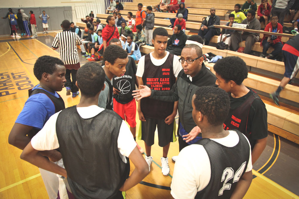 Coach Ar Ahmed rallies East African youth players in the Companion Athletics basketball league. The not-for-profit program is one of several trying to address a perceived generation gap in the community. (Photo by Alex Stonehill)