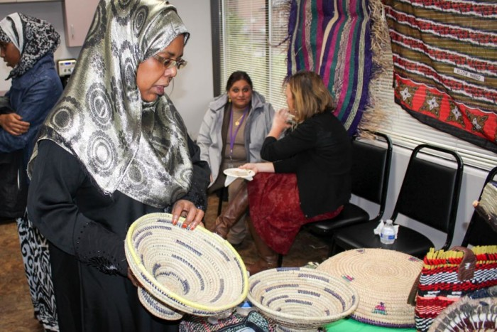 Social worker Farhiya Mohamed displays baskets and other items in a weaving group organized by International Counseling and Community Services. (Photo by Venice Buhain.)