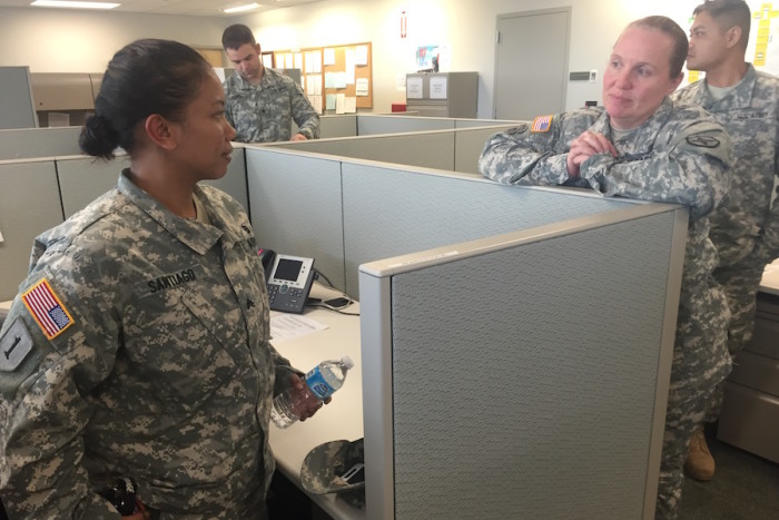 Sgt. Santiago (left) talks to Master Sgt. Georgia Warrix (right) at her cubicle at the Marysville Armed Forces Reserve Center as she packs up to leave on Sunday, November 15. (Photo by Kayla Roberts)