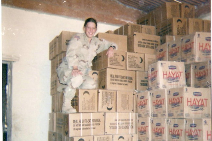 Stephanie Morgareidge sits on boxes of Meals Ready to Eat (MRE) and water supplies in Mosul, Iraq in 2003. Her job dealt with supplying , and her first job stateside at Home Depot as a receiving clerk fit into those skills. (Photo provided by Stephanie Morgareidge)