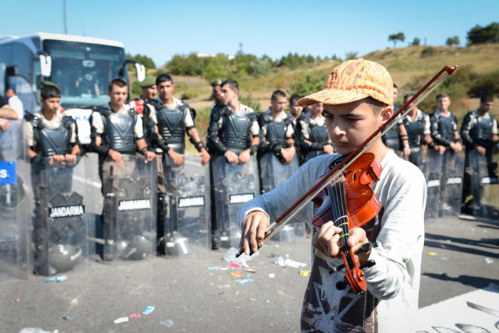 A young refugee plays violin in front of a line of Turkish police at Edirne, where refugees amassed hoping to cross into Greece. (Photo by Levent Kulu)