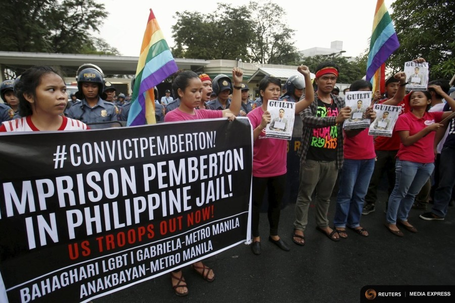 Activists hold a banner and images of U.S. Marine Lance Corporal Joseph Scott Pemberton, after he was found guilty by a trial court of killing Jennifer Laude, a transgender woman, during a rally for Laude outside the U.S. embassy in Manila, Philippines, December 1, 2015. (Photo by Erik De Castro for Reuters.)