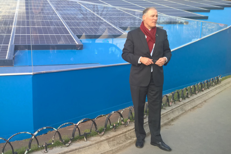 Jay Inslee standing next to a working solar installation in Paris (Photo by the Governors Office via Flickr.)