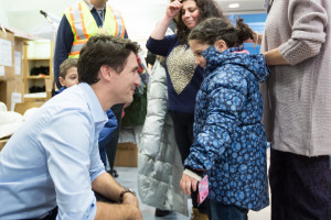 Canada Prime Minister Justin Trudeau is joined by Ontario Premier Kathleen Wynne as they hand out parts of a welcome package to newly arrived Syrian refugees. (Photo courtesy Prime Minister Justin Trudeau via Flickr.)