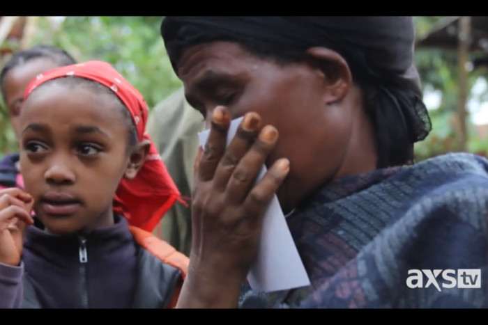 Almazay, a woman in Ethiopia, kisses a photo of her daughter, Senait, who was adopted in the United States. (Still from Unwanted in America)