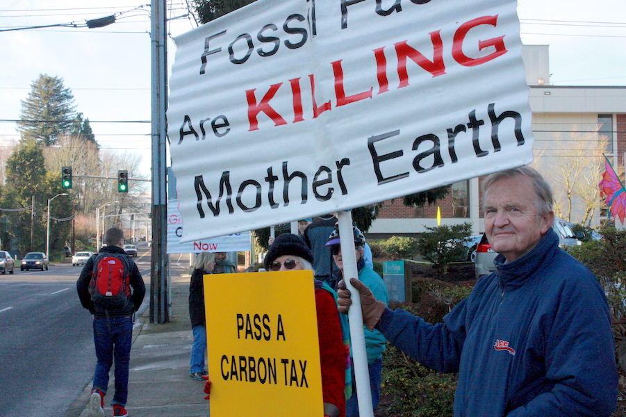 Frank Turner of Olympia holds up a sign in support of Initiative 732, a carbon tax that will go before the state legislature starting in January. (Photo by John Stang)