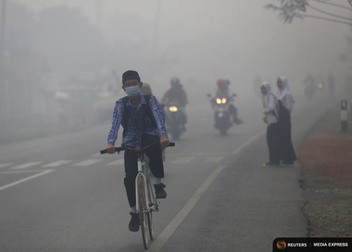 A boy rides his bike in the haze along an Indonesian highway in late October, at the height of forest fires that blanketed much of Southeast Asia in a haze. (Photo by REUTERS/Darren Whiteside)