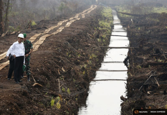 Indonesian President Joko Widodo inspects a newly-built canal to prevent underground spreading of peatland fires. Fires are out for now, but government officials warn they could be back as soon as February. (Photo by REUTERS/Darren Whiteside)