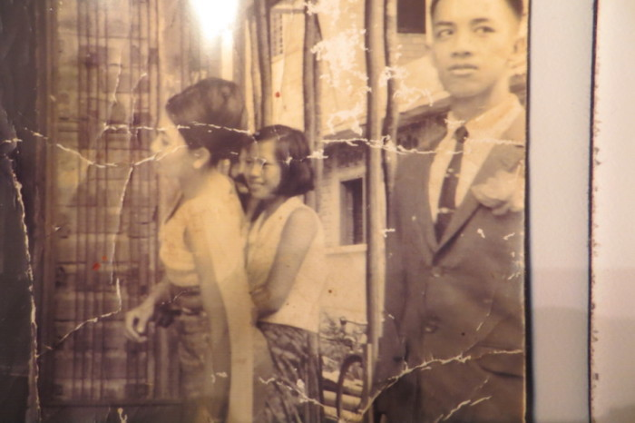 A tattered photo of the author's mother Sivorn (far left) and father Vuthy (far right) on their wedding day. (Photo courtesy of Samantha Pak)