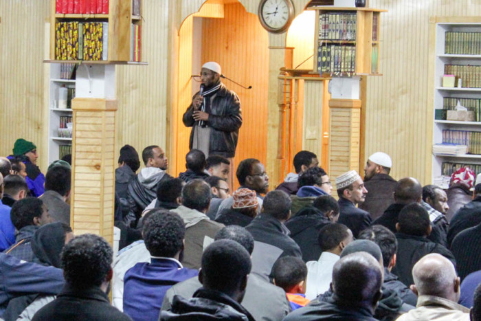 People gather at Abubakr Islamic Center in Tukwila before offering mid-day prayers, and a prayer for Hamza Warsame. (Photo by Venice Buhain.)