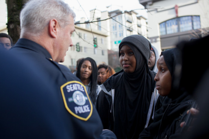 Captain Paul McDonaugh, commander of the Seattle Police Department's East Precinct, talks with Hamza Warsame's sister, Ikram, as the group stopped in front of the East Precinct building on 12th Avenue. He urged her and her family to share all of their grievances and concerns during their meeting with the Seattle Police Department tonight, according to Ikram Warsame. (Photo by Jovelle Tamayo.)