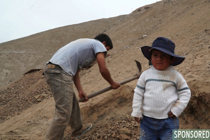 Kenneth stands by as his father, Alfredo, digs the foundation for their first home in Manchay. (Photo by Rustin Thompson)