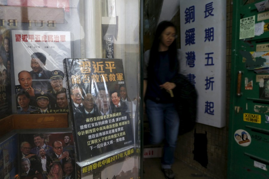A woman walks past a display cabinet of Causeway Bay Books displaying books critical of the Chinese leadership, in Hong Kong, China January 1, 2016. (Photo by Tyrone Siu for Reuters.)