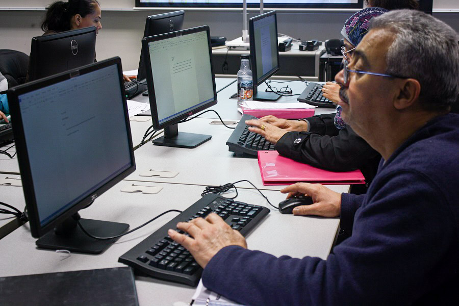 Qahtan Al Nidaw, a 64-year-old refugee and former news cameraman from Iraq, learns how to type on a computer. While he's an experienced cameraman, he's unfamiliar with using a computer. (Photo by Jane Koh)