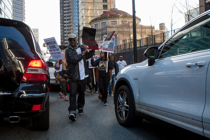 Tehuti Dagray, owner of Freedom Outreach Radio and a representative of the Black Prisoners Caucus, marches through traffic in downtown Seattle during a demonstration for Che Taylor, who was shot and killed Sunday by Seattle Police. (Photo by Jovelle Tamayo.)