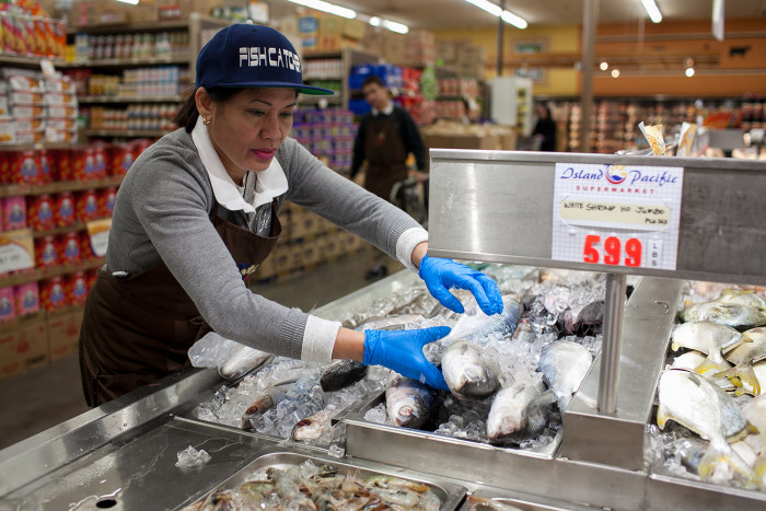 Amelda Orcejola handles seafood for a customer on February 24, 2016 at Island Pacific Market, a Filipino-inspired grocery store in Seattle's Rainier Valley. (Photo by Jovelle Tamayo.)