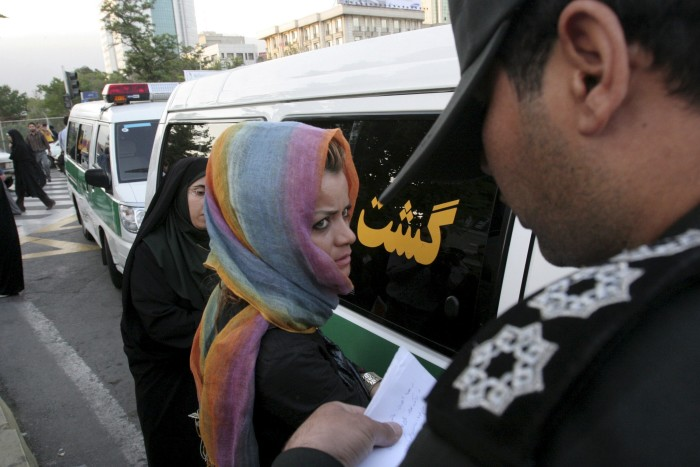 """Morality police take down the name of a detained woman during a crackdown on """"social corruption"""" in north Tehran in this June 18, 2008 file photo. (Photo by stringer for Reuters.)"""