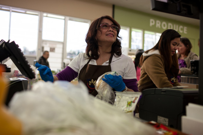 Susan Caberto rings up a customer's purchases on February 24, 2016 at Island Pacific Market, a Filipino-inspired grocery store in Seattle's Rainier Valley. (Photo by Jovelle Tamayo.)