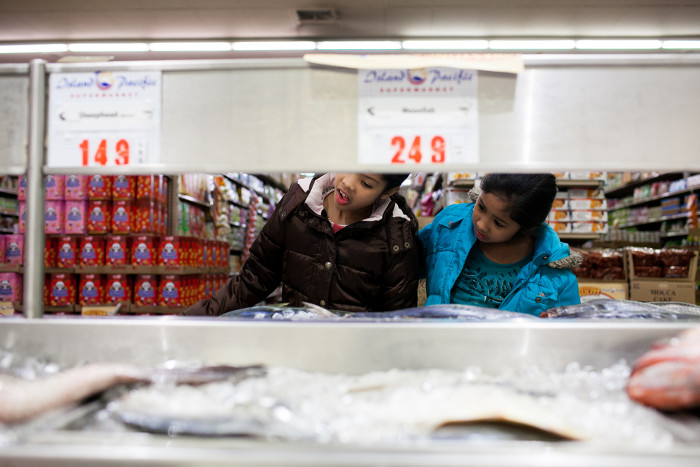 Dayana and Sheyla Aguilar examine fish while their mother shops on February 18, 2016 at Island Pacific Market, a Filipino-inspired grocery store in Seattle's Rainier Valley. (Photo by Jovelle Tamayo.)
