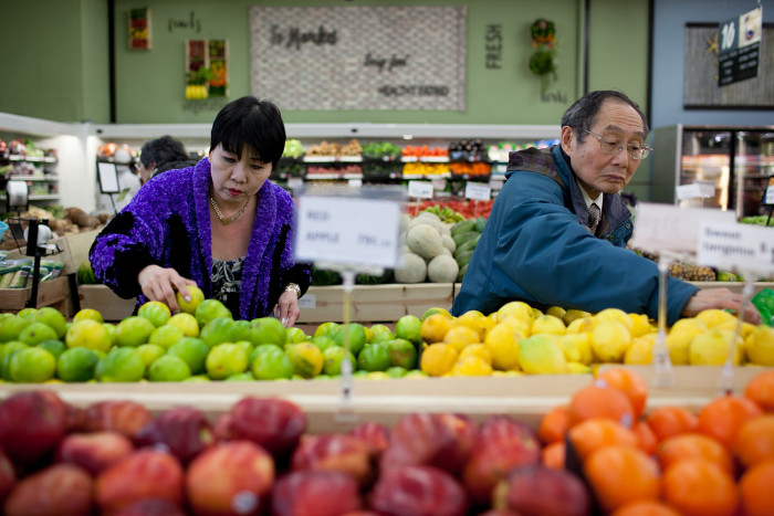 Shoppers choose fruit at Island Pacific Market, a Filipino-inspired grocery store in Seattle's Rainier Valley. (Photo by Jovelle Tamayo.)