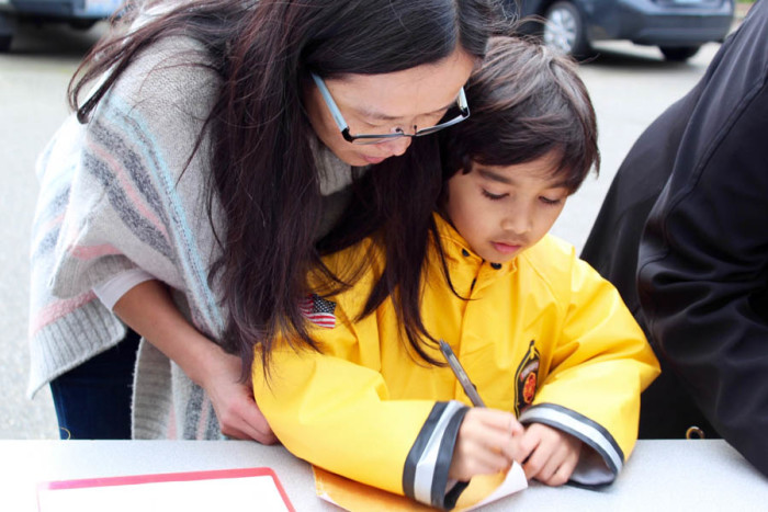 Yinglin Perera helps her son Ishan, 6, write an anti-racism message to add to a display that is traveling the Eastside. (Photo by Venice Buhain.)