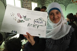 "A Syrian girl holds up a poster she drew ""about how she recently helped someone using information or technology"" during UW professor Karen Fisher's workshop at Za'atari refugee camp in Jordan in January 2015. (Photo courtesy of Karen Fisher, University of Washington Information School)"