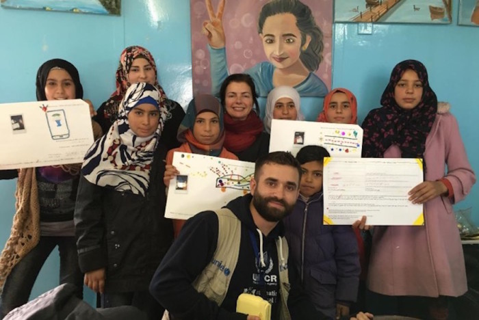 UW professor Karen Fisher (center, back row) and a UNHCR interpreter (center, front row) pose with Syrian teens holding Magic Genius Device prototypes they created during a participatory design workshop at Za'atari Refugee Camp in Jordan in November 2015. (Photo courtesy of Karen Fisher, University of Washington Information School)