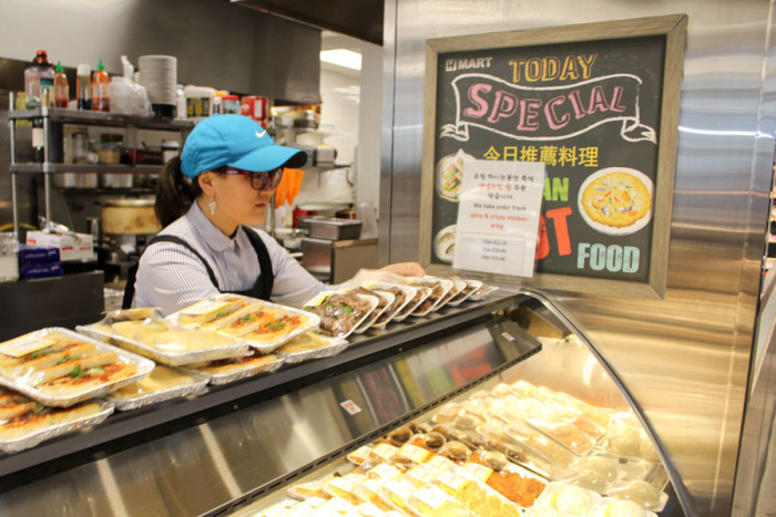 Cashier Susie Hughes arranges the lunchtime deli offerings at the Bellevue H-Mart. (Photo by Venice Buhain.)