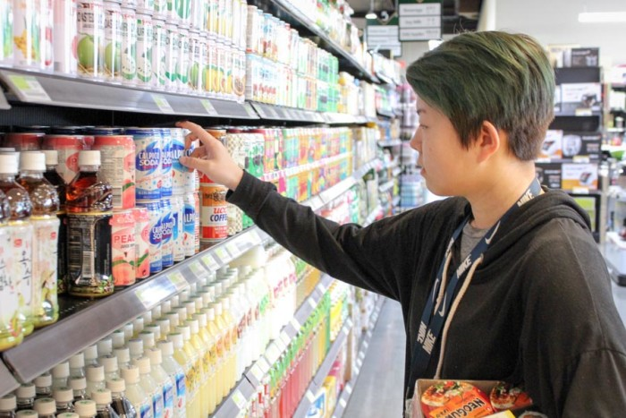 Bellevue High School student Jennifer Morss picks out a drink as she stops at the Bellevue H-Mart for lunch. (Photo by Venice Buhain.)