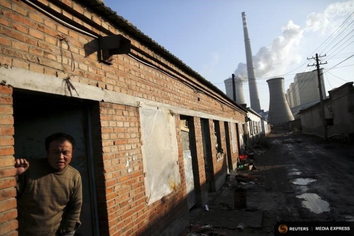 A migrant worker steps out of his home next to a coal power plant in Beijing. (Photo from REUTERS / Damir Sagolj)