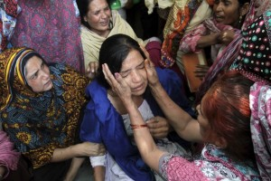 Family members comfort a woman mourns the death of a relative, who was killed in a blast outside a public park on Sunday, during funeral in Lahore, Pakistan, March 28, 2016. (Photo by Mohsin Raza for Reuters.)